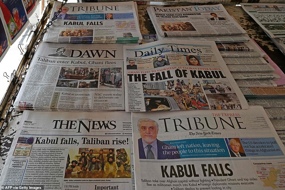 Pakistan's newspapers are pictured displaying front page news about Afghanistan, at a stall in Islamabad on August 16, 2021 after the Taliban were in control of Afghanistan after President Ashraf Ghani fled the country and conceded the insurgents had won the 20-year war