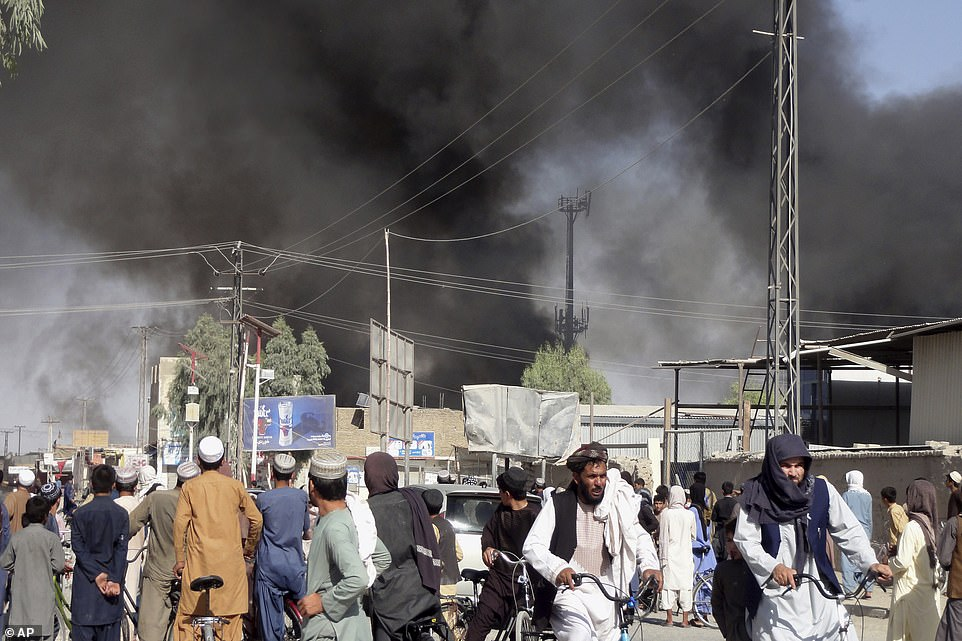 People flee as smoke rises after fighting between the Taliban and Afghan security personnel in Kandahar, Afghanistan
