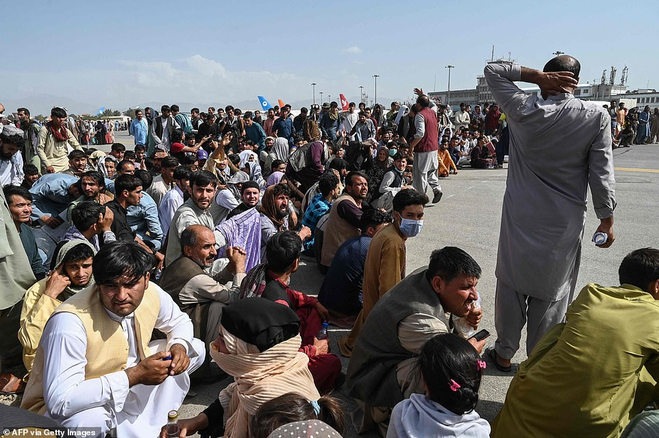 Hopeful Afghan passengers wait at Kabul airport as hundreds of US and UK citizens are evacuated following the Taliban's swift campaign
