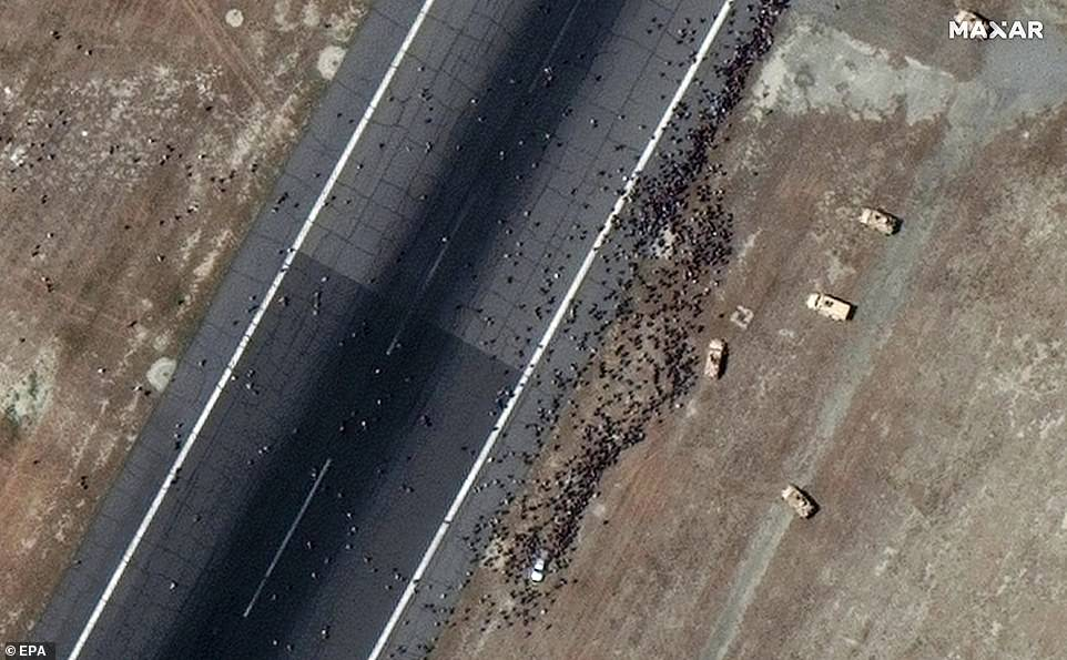 A satellite image shows crowds of Afghans gathered on the tarmac at Hamid Karzai airport on Monday as they desperately try to board the last flights out of Kabul