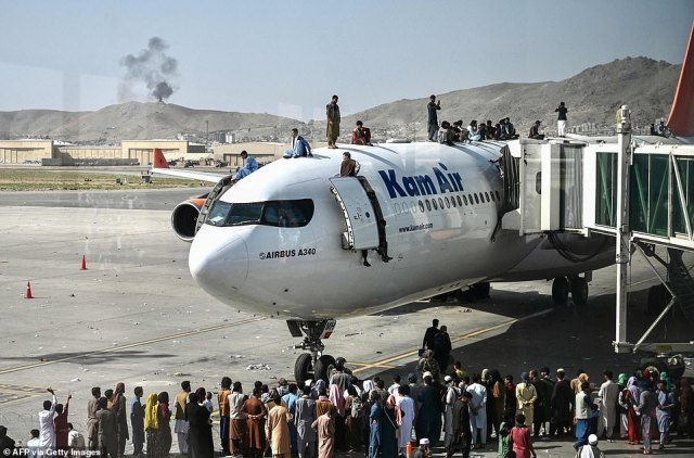 Afghans climb on top of a passenger jet at Kabul's airport amid chaotic scenes as civilians try to find safe passage out of the Afghan capital after Taliban takeover
