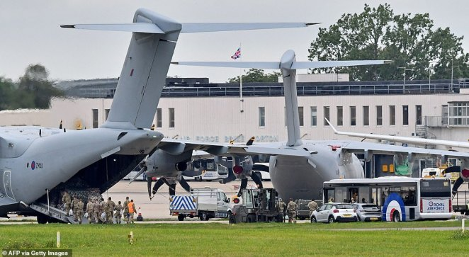 Military personnel board a Royal Air Force Airbus A400M transport plane, after arriving by bus at RAF Brize Norton yesterday, as Britain sends 900 soldiers back to Afghanistan over the coming days to help with repatriations and evacuations