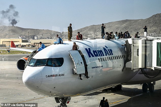Afghan people climb atop a plane as they wait at the airport in Kabul on August 16, 2021, after a stunningly swift end to Afghanistan's 20-year war, as thousands of people mobbed the city's airport trying to flee the group's feared hardline brand of Islamist rule