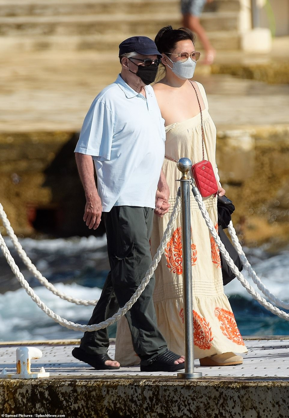 Holiday style:He kept things comfortable in a pair of black slider sandals while his female companion looked elegant in a cream maxi dress