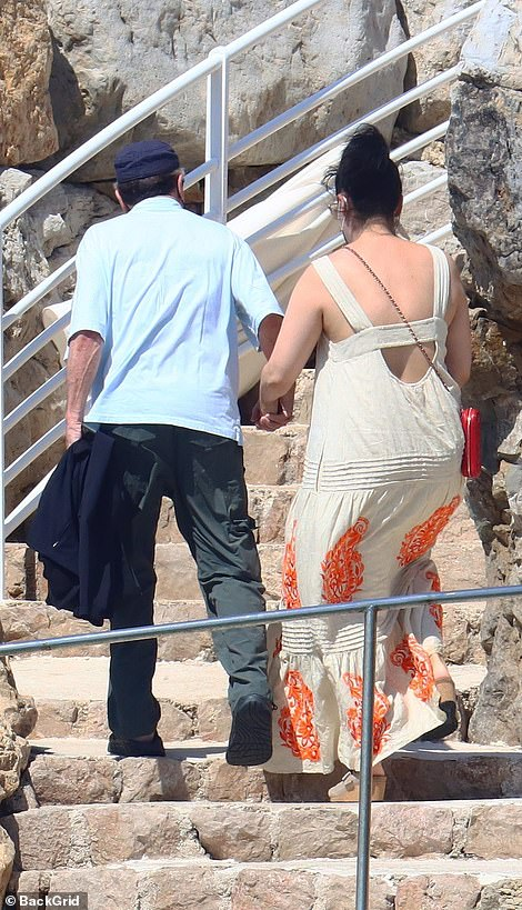 Sunny days: The brunette beauty caught the sun in her billowing maxi dress with cut-out detail at the back