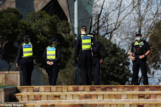 Police are seen on patrol at Federation Square on Tuesday in Melbourne, Australia to enforce lockdown rules (pictured) as the city endures among the world's strictest lockdowns