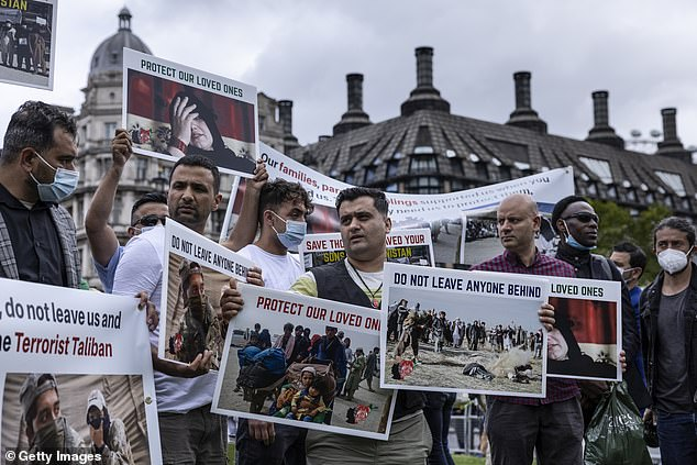 A large group of protesters huddle together at Parliament Square today demanding that the Government safely return Brits left in Afghanistan