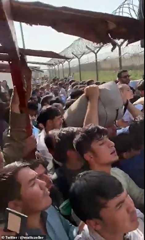 Afghans crowd the gate at Kabul airport