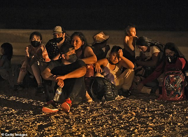 A group of migrants sit and wait as they are detained by U.S. Customs and Border Protection Sunday in San Luis, Arizona