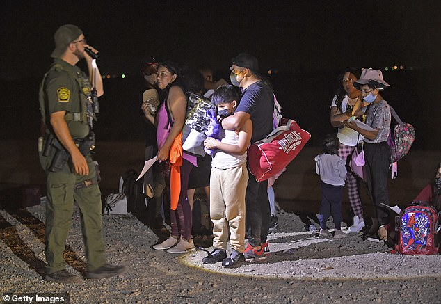 A U.S. Customs and Border Protection officer shines a flashlight on a group of migrants who have entered the U.S. from Mexico