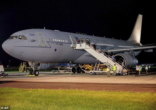 British nationals and Afghan evacuees disembark a flight from Afghanistan at RAF Brize Norton in England on Tuesday