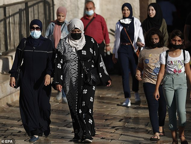 Palestinian women are pictured wearing face masks in the street in Jerusalem on Thursday