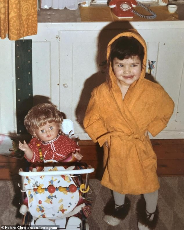 Having a blast: Sending her followers even further back in time to her pre-school years, the future photographer posed in a chic orange dressing gown alongside a doll in a pushchair