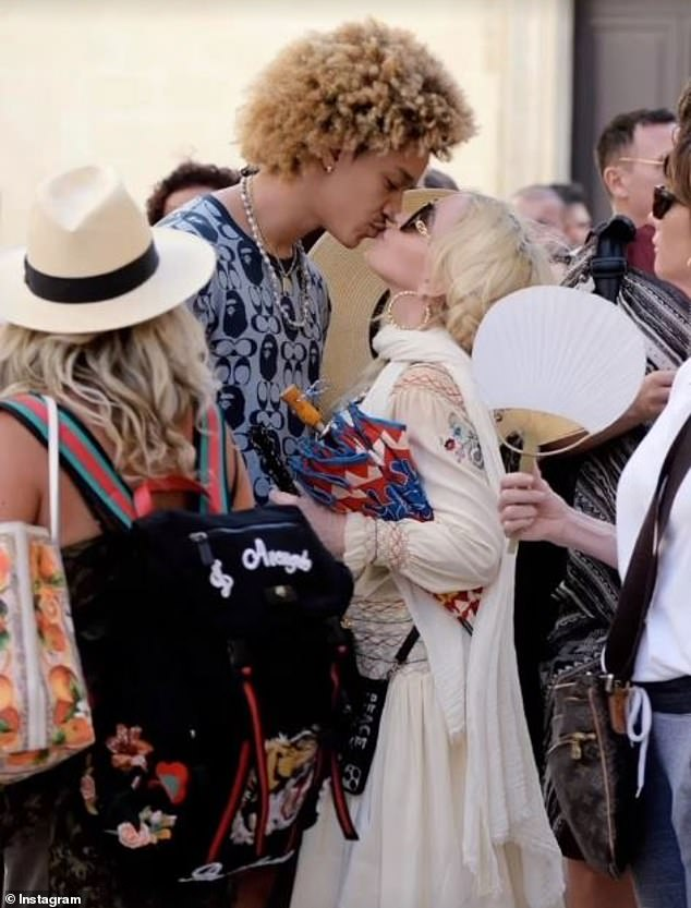 Loved-up: Outside of the church, Madonna put on a PDA display with her boyfriend Ahlamalik - who is 36 years her junior - as they kissed passionately in the street