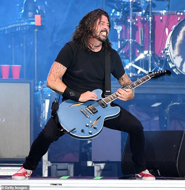 Back at it: Grohl also pointed out that returning to touring has 'brought a new energy to us after all of these years'; he is seen playing at Lollapalooza earlier this month