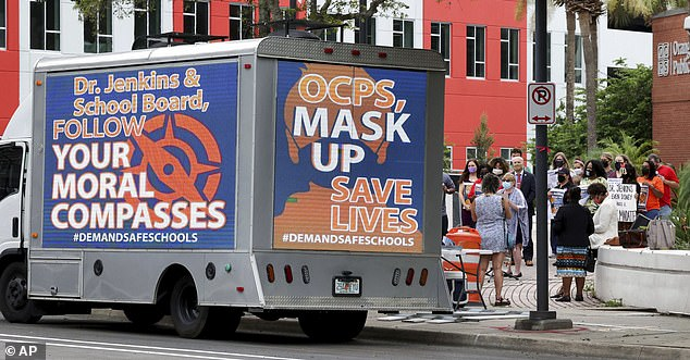 A mobile billboard truck displays messages for the Orange County Public Schools board during a protest in favor of masks, in front of the OCPS headquarters in downtown Orlando on Monday