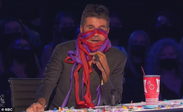 Wrapped up:Simon Cowell wrapped confetti streamers around his face after watching entertainer Keith Apicary perform a haphazard dance routine Tuesday on America's Got Talent