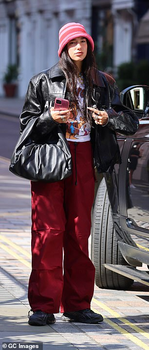 Get-up: Dua wore a white band T-shirt beneath her Balenciaga jacket and strolled along in baggy, parachute-like trousers and grey trainers