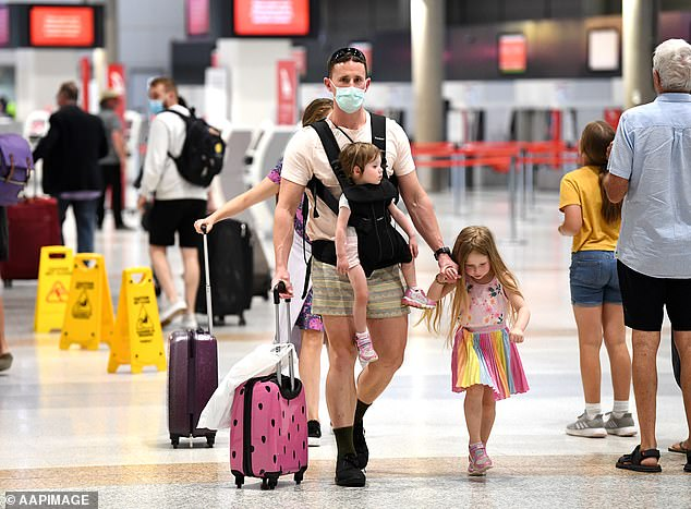 For the next fortnight people entering Queensland will not be permitted to enter on a right of entry pass and would need to reapply for a border pass (pictured - travellers wearing masks in Queensland)