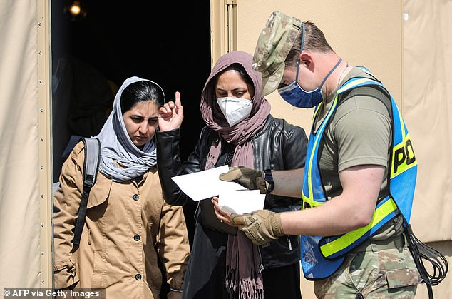 A member of ther US military speaks with Afghan evacuees at the US Air Base Ramstein, Germany on August 26, 2021.'There¿s no substitute for a young man or woman, a young U.S. man or woman conducting a search' at the airport, said McKenzie