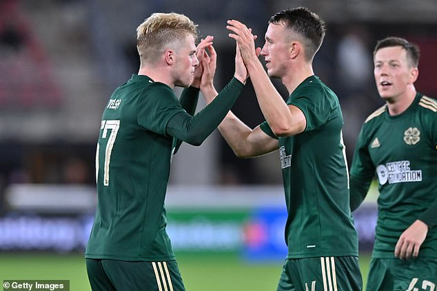 Stephen Welsh (left) and David Turnbull (right) celebrate Celtic qualifying for the group stage