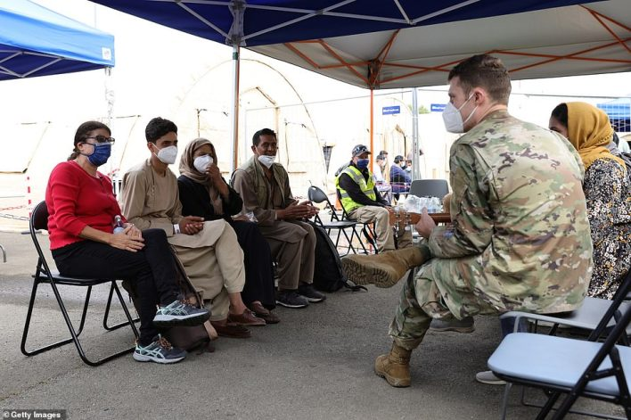 A U.S. military officer plays a ukulele for evacuees from Afghanistan at a waiting area at Ramstein Air Base on August 26