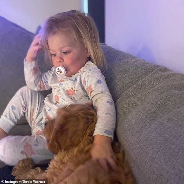 Isla's mate: In one image, baby Isla gets up-close-and-personal on the couch with Cookie