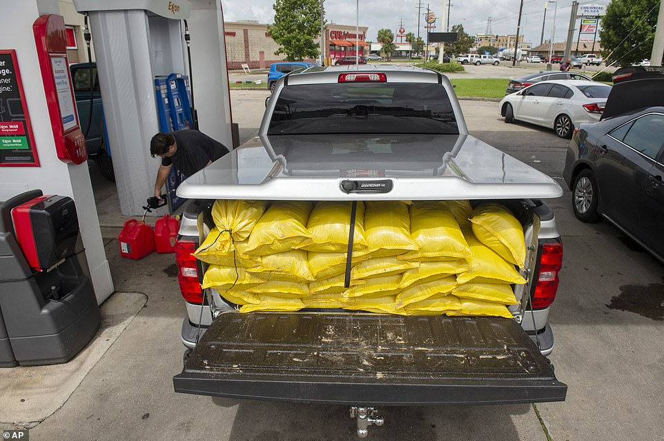 Retired Louisiana State Trooper Troy Leonard (pictured left) helps to distribute sandbags to his family on Saturday