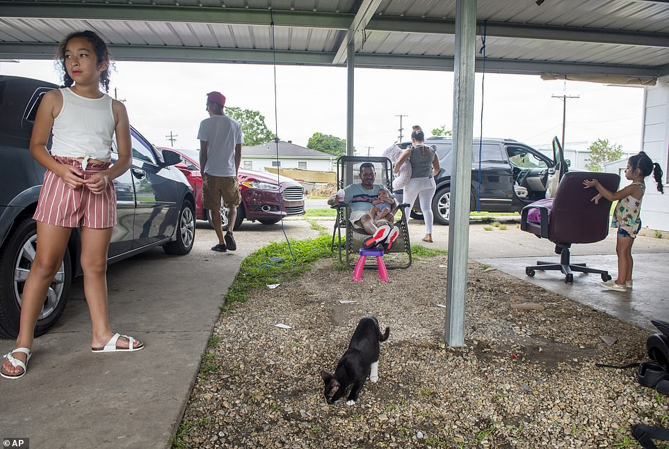 Isis Alvarado, 10, and her sister Yulcigi wait for their family to finish packing their car with essential belongings before they evacuate to Florida from Morgan City Louisiana on Saturday