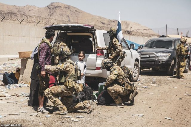 Finnish coalition forces assist evacuees for onward processing during an evacuation at Hamid Karzai International Airport earlier this week