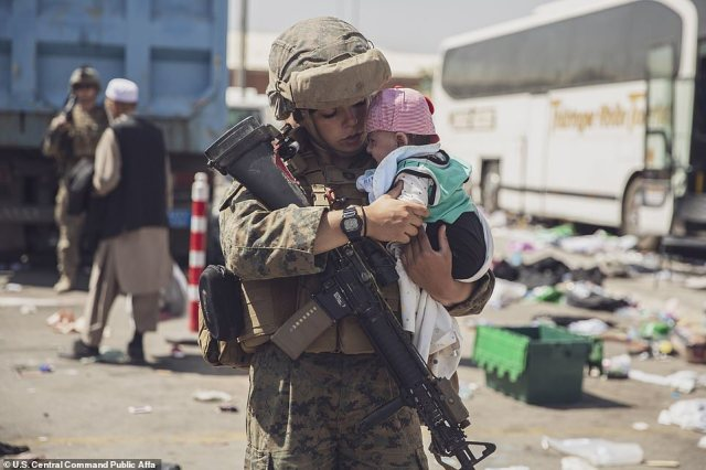 A United States Marine with the 24th Marine Expeditionary Unit carried a baby as its family passed through the Evacuation Control Center at Hamid Karzai International Airport in Kabul
