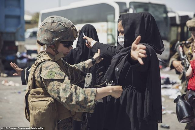 A US Marine with the 24th Marine Expeditionary Unit checks an Afghan woman as she goes through the Evacuation Control Center during an evacuation at Hamid Karzai International Airport