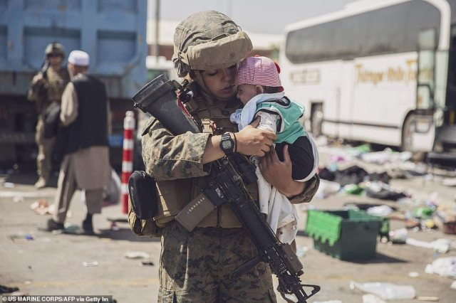 A US Marine with the 24th Marine Expeditionary Unit carrying a baby as the family processes through the Evacuation Control Center today