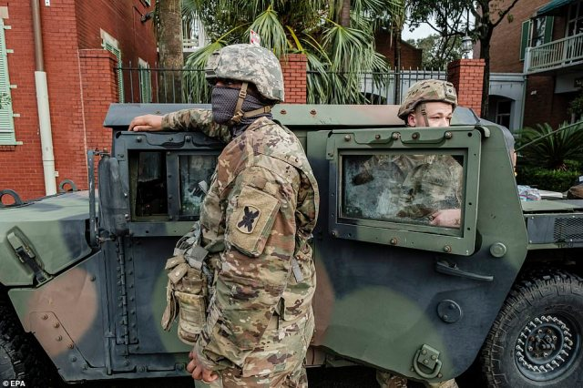 Members of the Louisiana National Guard stood outside their vehicleson North Rampart Street, in the French Quarter, to help in Hurricane Ida recovery efforts on Monday