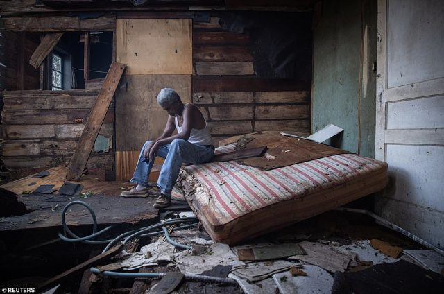 Charles sits dejected on a mattress inside his home after Ida tore through Sunday, bringing 150mph winds and severe floods
