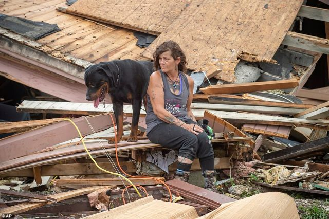 Fran Tribe and her dog, Dave, sit outside home destroyed by Hurricane Ida in Houma, Louisiana