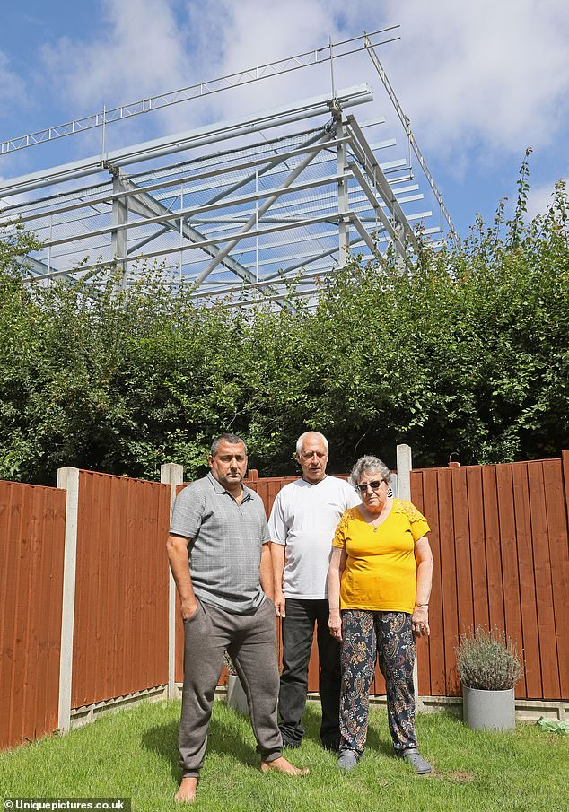 Andy Parker, 55 (left), with neighbours Dave and Lynn Snell, who all claim the warehouse (seen above them) has knocked tens of thousands of pounds off the value of their properties in Harlow, Essex