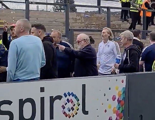 Fans have hailed the Macclesfield director of football for stepping in after 'cans were thrown and smoke bombs let off' in the stands, with some throwing punches