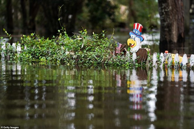 Floodwaters nearly top a fence decorated with a patriotic display in Kiln, Mississippi on Monday