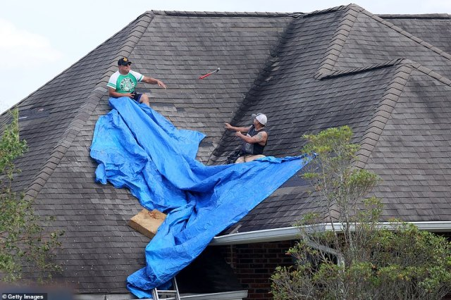 Workers tarp a roof after it was damaged by Hurricane Ida in LaPlace, Louisiana on Monday
