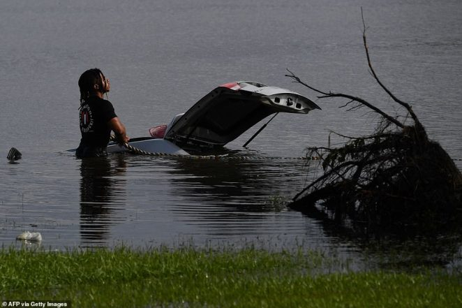 A person uses a rope to try and tow a submerged car out of flood waters in LaPlace, Louisiana