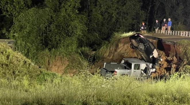 Pictured: Highway Patrol officers assess the scene of a highway collapse in which two people were killed late on Monday