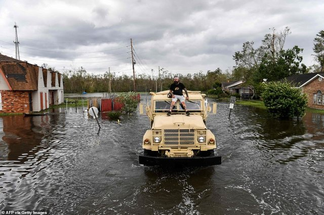 A volunteer rides on top of a high water truck searching for people who may still be trapped inside their flooded homes