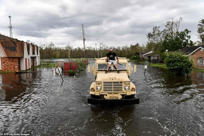 A volunteer rides on top of a high water truck with a chainsaw to cut branches as they volunteer to help evacuate people from homes after neighborhoods flooded in LaPlace, Louisiana on August 30, 2021 in the aftermath of Hurricane Ida