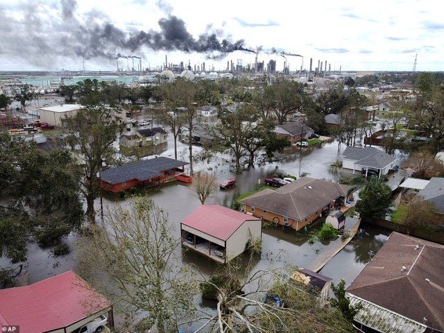 Homes near Norco, La., are surrounded by floodwater as chemical refineries continue to flare the day after Hurricane Ida hit southern Louisiana, Monday, Aug. 30, 2021