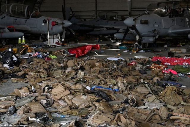 Afghan Air Force's A-29 attack aircraft and armoured vests are left on the ground inside a hangar at the airport in Kabul