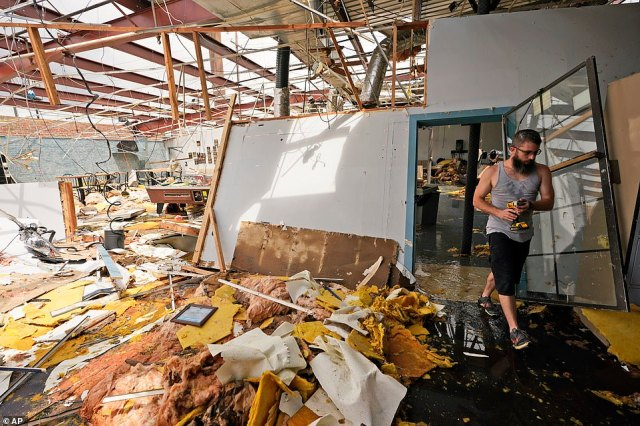 A local volunteer surveys damage done to a local bowling alley in Houma, Louisiana on Tuesday