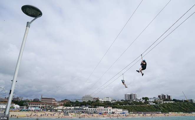People zip wire across the sea from Bournemouth pier towards the beach earlier this month.Despite the soggy outlook, bookmaker Coral has slashed the odds from 3-1 to 6-4 on next month being a record hot September in the UK