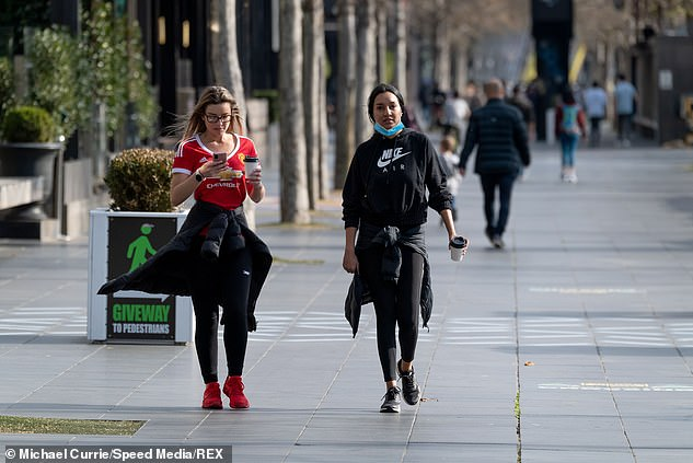 'If we were to open up — this is the thing with Delta — you either aim for zero or a very low number and therefore keep the numbers low,' Premier Andrews said (pictured, two women enjoy a coffee as they walk along South Bank in Melbourne on Tuesday)