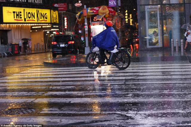 MANHATTAN, NEW YORK CITY: A food delivery driver rides on a motorized bike as he works during the storm